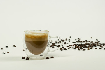 Coffee with milk in modern cup on white background with coffee beans