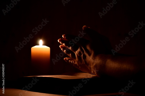 Cuadros en Lienzo  Religious prayer with a candle in complete darkness
