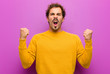 Leinwandbild Motiv young handsome man shouting aggressively with an angry expression or with fists clenched celebrating success against purple wall