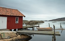Red Cabin On A Wooden Pier And...