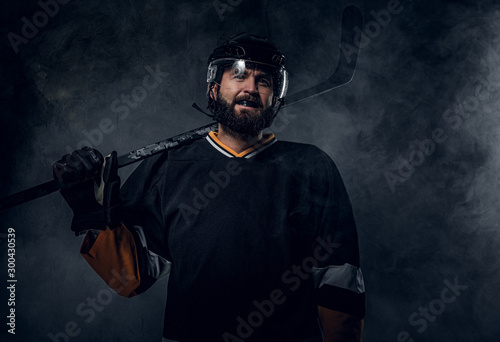 Happy toothless hockey player is posing for photographer with hockey stick Wallpaper Mural