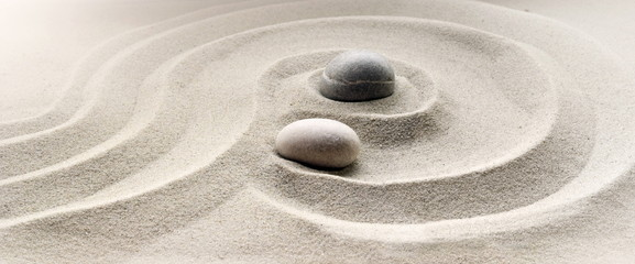 zen garden meditation stone background with stones and lines in sand for rela...