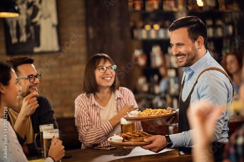 Photo Happy waiter serving food to guest who are drinking beer in a pub