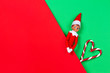 canvas print picture - Christmas background. Toy santa elf and candy canes on red and green background. Top view
