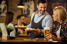 Happy Waiter Giving Nachos To A Woman Who Is Drinking Beer In A Pub.