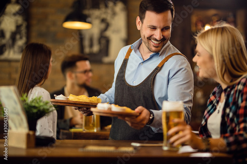 Happy waiter giving nachos to a woman who is drinking beer in a pub Wallpaper Mural