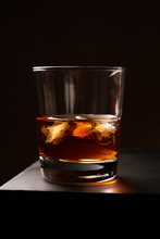 A Glass Of Whiskey With Ice On...
