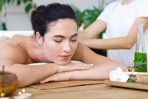 Garden Poster Spa Young pleased woman is getting thai massage, therapy. Female hands of master are kneading back of client. Brunette girl is lying on couch in light spa ayurveda salon. Relax and health care concept.