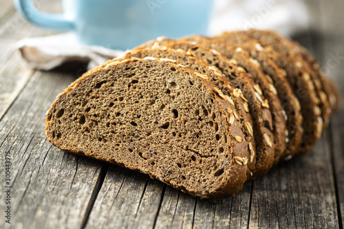Tuinposter Brood Sliced whole grain bread with oat flakes. Wholemeal bread.