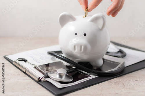 Fotomural  Woman puts coin in the piggy bank