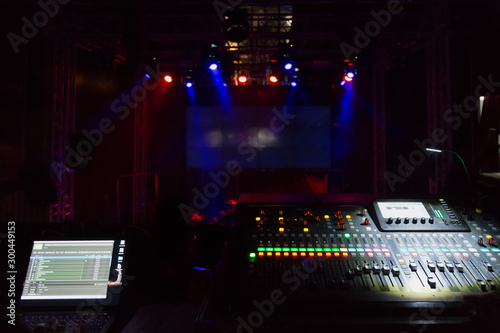 Fototapeta  Audio sound mixer console with buttons and sliders against the concert scene