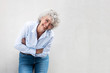 canvas print picture - older woman laughing with arms crossed by gray wall
