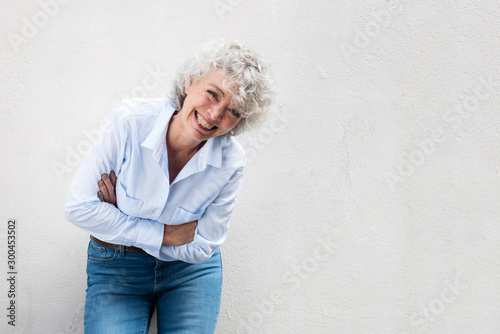 Fotografia older woman laughing with arms crossed by gray wall