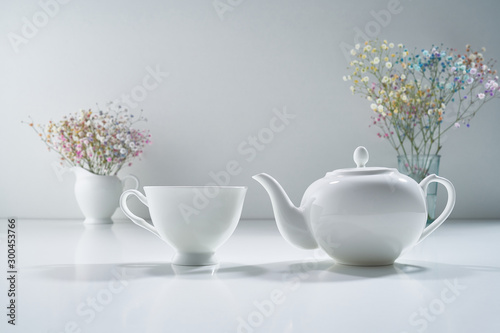 Composition with white porcelain tea-ware on a light gray background with a delicate bouquet of flowers