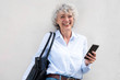 canvas print picture - middle aged woman smiling with bag and mobile phone by white background