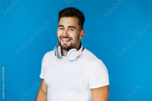 Photographie  Smiling handsome man holds his headphones on the neck and looks at the camera