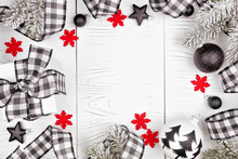 Christmas Frame Of Black And White Checked Buffalo Plaid Ribbon, Gifts And Ornaments. Top View On A White Wood Background.