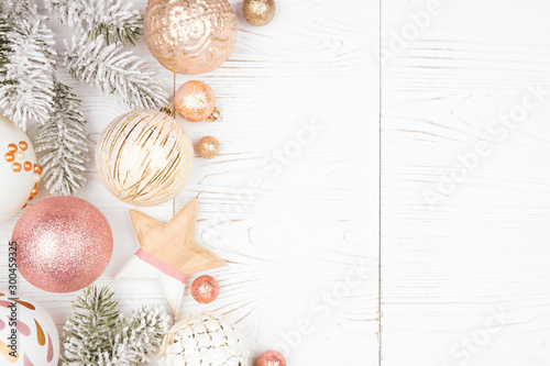 Poster Ecole de Danse Christmas side border of snowy branches and dusty rose, gold, and white ornaments. Top view on a white wood background.