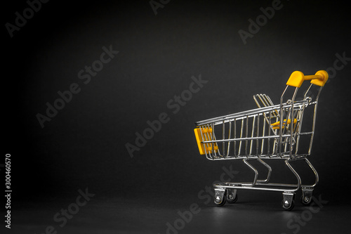 Pinturas sobre lienzo  Empty shopping trolley on dark toned background with some copy space, financial