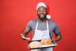 Leinwanddruck Bild - Christmas bakery. Crazy young african american male chef cook or baker man in striped apron grey t-shirt posing isolated over red background. Cooking food concept. Mock up copy space.