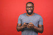 canvas print picture - Portrait of handsome excited cheerful joyful delightful african american guy wearing casual sending and getting messages to his lover isolated against red background. Using phone.
