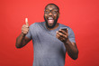 canvas print picture - Afro american man using smartphone over isolated red background happy with big smile doing ok sign, thumb up with fingers, excellent sign.