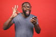 canvas print picture - Afro american man using smartphone over isolated red background doing ok sign with fingers, excellent symbol.