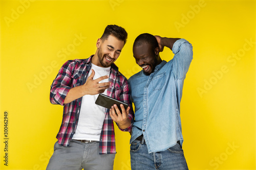 european and afroamerican guys are looking on the tablet and laughing on the yel Canvas Print