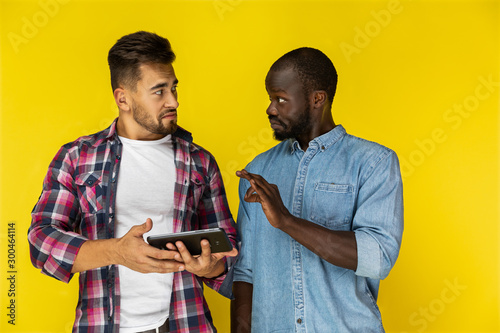 Photo afroamerican guy is proving smth to european guy  in informal shirts on the yell