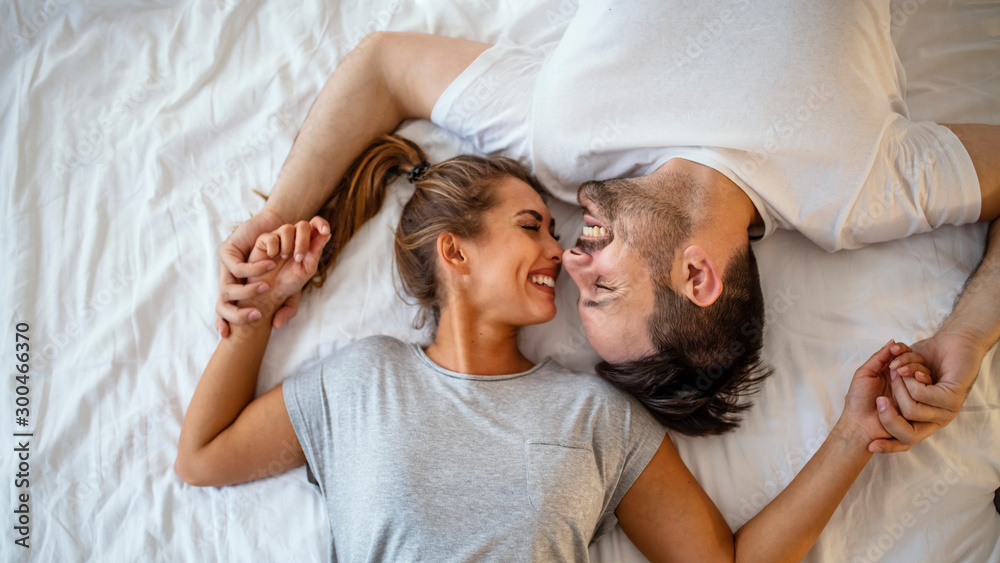 Fototapety, obrazy: Guy and a girl in a cozy home environment. Happy man and woman lying in the bedroom stock photo. Top view of smiling young couple cuddling in bed in morning.  Beautiful pair of lovers hug and kiss