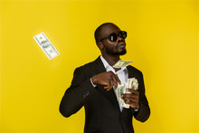 Bearded Solid Young Afroamerican Guy Is Throwing Out Dollars From One Hand, Wearing Sunglasses And Black Suit On The Yellow Background