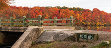Be Kind Is Written Next To Bridge Over Waterall At Southards Pond With Autumn Coloredl Leaves In Background
