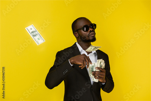 Fotografía bearded solid young afroamerican guy is throwing out dollars from one hand, wear