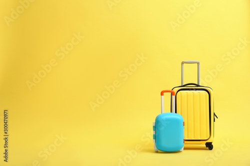 Stylish suitcases on yellow background, space for text