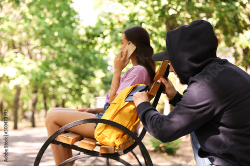 Fotografía  Thief stealing wallet from backpack of careless woman talking on mobile phone in
