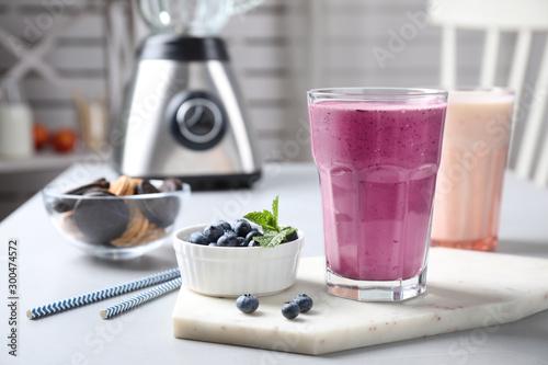 Tasty milk shake and blueberries on white table Wallpaper Mural