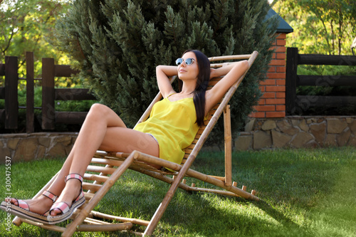 Photographie Beautiful young woman relaxing in deckchair at garden