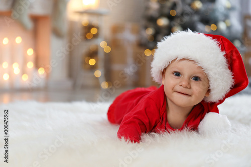 Fotobehang Hoogte schaal Little baby wearing Santa hat on floor at home. First Christmas