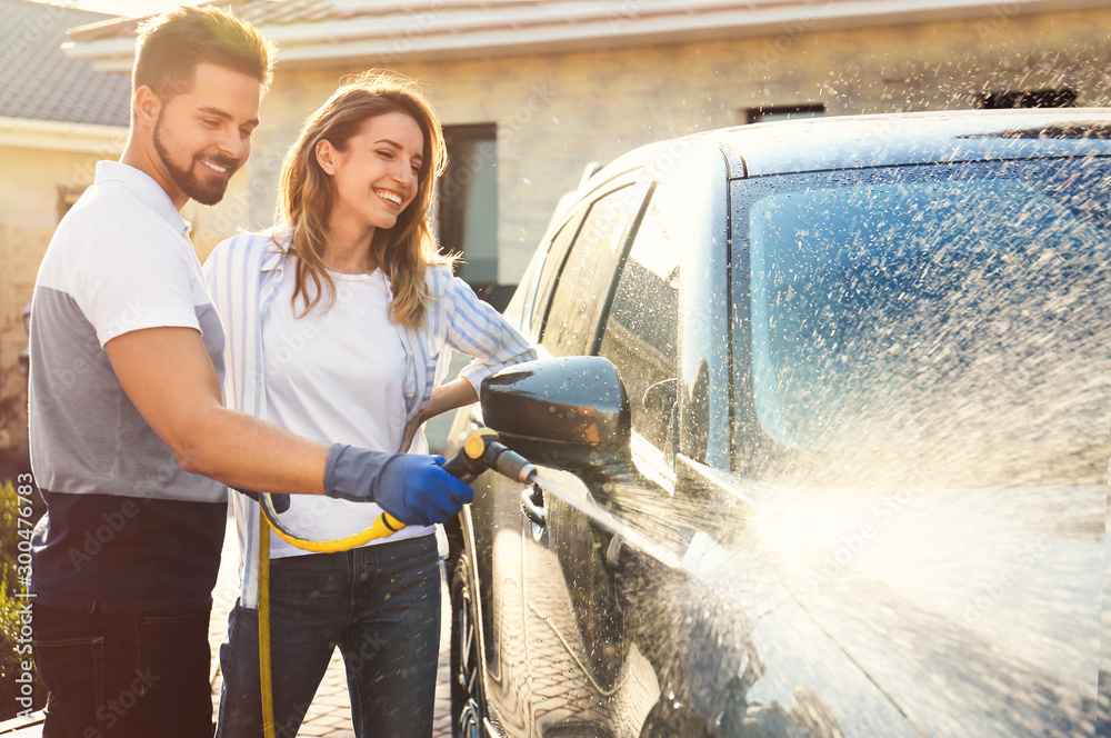 Fototapety, obrazy: Happy young couple washing car at backyard on sunny day