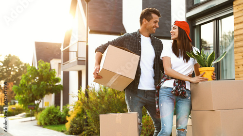 Obraz Happy couple with moving boxes and household stuff near their new house on sunny day - fototapety do salonu