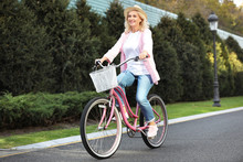 Mature Woman Riding Bicycle Outdoors. Active Lifestyle