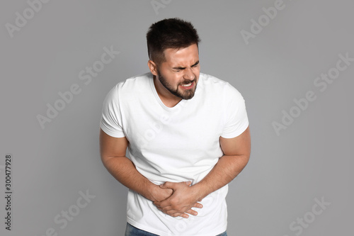 Man suffering from abdominal pain on light grey background Wallpaper Mural