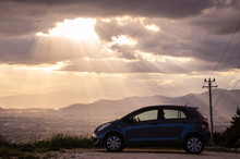 View Of A Car On Top Of A Hill With The City In The Background In Some Dramatic Light With Sun Rays
