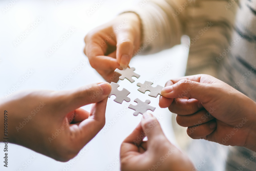 Fototapeta Closeup image of many people holding and putting a piece of white jigsaw puzzle together