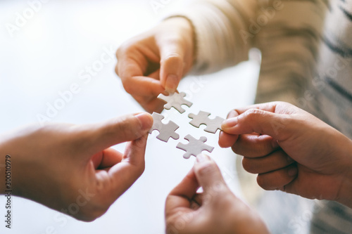 Obraz Closeup image of many people holding and putting a piece of white jigsaw puzzle together - fototapety do salonu