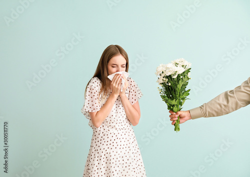 Photo Man giving flowers to young woman suffering from allergy on light background