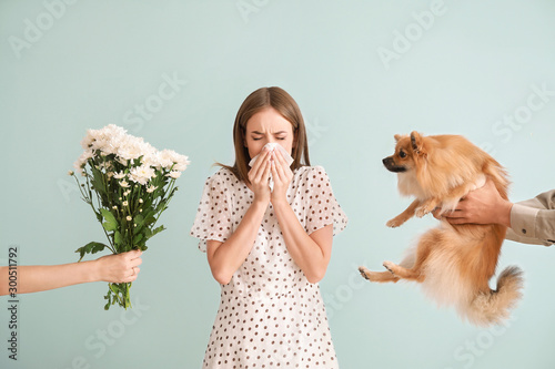 Fotografía People giving flowers and dog to young woman suffering from allergy on light bac
