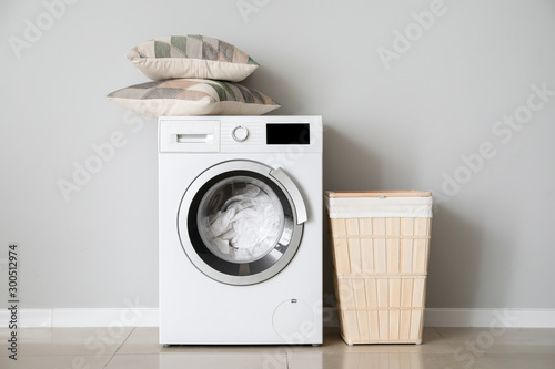 Fotomural  Modern washing machine with laundry near white wall