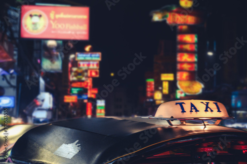 Tuk-Tuk Taxi sign with defocused lights blur in Chinatown in Bangkok at night , Thailand , Southeast asia