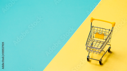Foto Empty miniature shopping cart on blue and yellow background